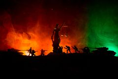 战争没有正义概念 与场面和正义战斗的雕象在黑暗的被定调子的有雾的背景的军事剪影 库存图片