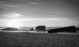 战争碉堡剪影在美好的温暖的金黄日落风景的与飞溅在大西洋海岸背景挥动 免版税图库摄影