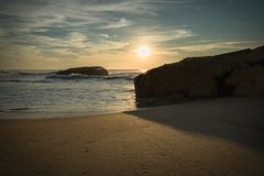 战争碉堡剪影在风景美好的沙滩海景的与在大西洋的波浪在wa的蓝色金黄日落天空的 图库摄影