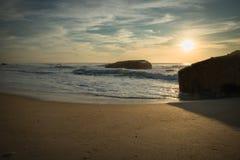 战争碉堡剪影在风景美好的沙滩海景的与在大西洋的波浪在wa的蓝色金黄日落天空的 免版税库存照片