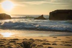 战争碉堡剪影在风景美好的沙滩海景的与在大西洋的波浪在wa的蓝色金黄日落天空的 免版税库存图片
