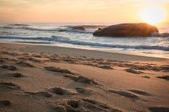 战争碉堡剪影在风景美好的沙滩海景的与在大西洋的波浪在wa的蓝色金黄日落天空的 库存照片