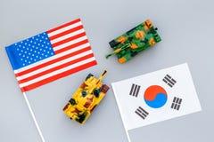 战争,交锋概念 韩国,美国 坦克在灰色背景顶视图的韩国和美国国旗附近戏弄 免版税库存图片