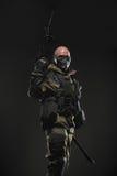 战士人举行在黑暗的背景的机枪 免版税图库摄影