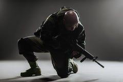 战士人举行在黑暗的背景的机枪 库存图片