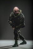 战士人举行在黑暗的背景的机枪 免版税库存照片