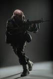 战士人举行在黑暗的背景的机枪 库存照片