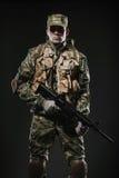 战士人举行在黑暗的背景的机枪 免版税库存图片