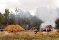 战士保卫一个灼烧的村庄 免版税库存图片