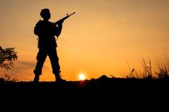 战士和枪在剪影射击 免版税库存照片
