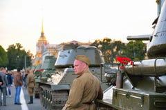 战士和红色康乃馨在枪轰击框和一个箱子与 库存照片