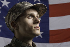 年轻战士在美国国旗前面摆在了,水平 图库摄影