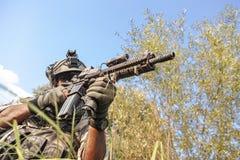 战士射击在山的军事行动时 库存图片