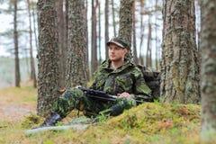 年轻战士或猎人与枪在森林里 免版税库存图片