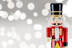 战士站立在圣诞灯前面的胡桃钳雕象 免版税库存照片