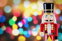 战士站立在圣诞灯前面的胡桃钳雕象 库存图片