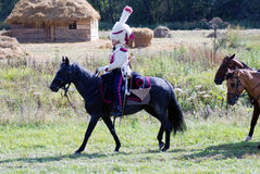 战士骑一匹黑马。 图库摄影