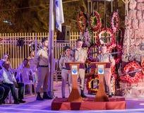 战士-纪念仪式立场的参加者在一个警报器期间的在半被上船桅的旗子附近在下落的纪念站点 免版税库存图片