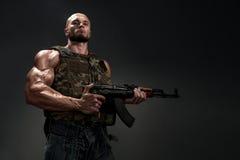 战士画象有一杆枪的在黑背景 免版税图库摄影