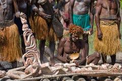 战士Asmat部落坐并且雕刻一个礼节雕象 免版税库存图片
