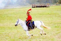 战士reenactor在红色乘驾穿戴了一个白马 免版税库存图片