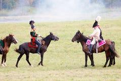 战士reenactors骑棕色马 背景夫妇查出的纵向配置文件空白年轻人 库存照片