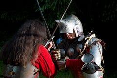 战斗与剑的两个骑士在森林在晚上 免版税库存照片