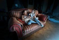 战斗为在沙发的电视遥控的两个女孩在晚上 库存照片
