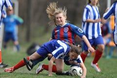 战斗为球的女孩在足球赛期间 免版税图库摄影