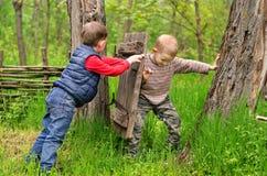 战斗在一个土气老门的两个年轻男孩 免版税库存照片