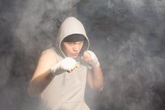 战斗在充满烟雾的大气的年轻拳击手 图库摄影