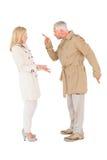 战斗在军用防水短大衣的恼怒的夫妇 库存图片