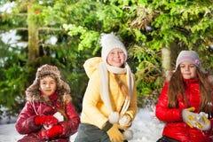 战斗在冬天森林里的三个女孩雪球 库存照片