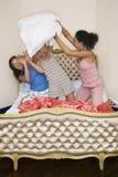 战斗在床上的十几岁的女孩枕头 免版税库存图片