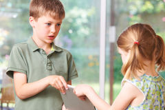 战斗在数字式片剂的男孩和女孩 免版税库存图片
