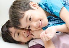 战斗在沙发的小兄弟姐妹男孩 免版税库存照片