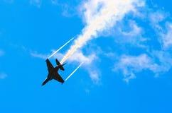 战斗机在蓝天特技飞行的烟飞行 库存图片