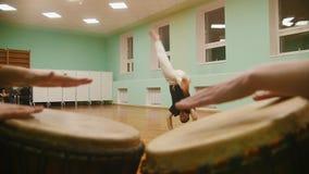 战斗机执行军事把戏与在播放一两个乐器atabaque的背景的舞蹈元素 股票录像
