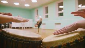 战斗机执行军事把戏与在播放一两个乐器jembe或atabaque的背景的舞蹈元素 股票视频