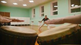 战斗机执行军事把戏与在播放一两个乐器jembe的背景的舞蹈元素 股票录像