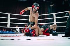 战斗机被混合的武术吹朝向说谎在地板上的对手 免版税图库摄影