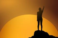 战斗的妇女剪影站立和举她的手和两手指在庆祝的日落或日出的 企业概念查出的成功白色 库存照片