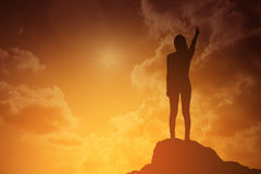 战斗的妇女剪影站立和举她的手和两手指在庆祝的日落或日出的 企业概念查出的成功白色 免版税库存图片