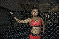 战斗的手套和体育的美丽和性感的亚裔战斗机妇女穿衣在MUTTAHIDA MAJLIS-E-AMAL笼子摆在凉快里面 免版税库存照片