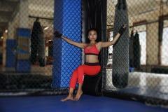 战斗的手套和体育的美丽和性感的亚裔战斗机妇女穿衣在MUTTAHIDA MAJLIS-E-AMAL笼子摆在凉快里面 免版税库存图片