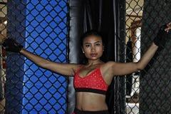 战斗的手套和体育的美丽和性感的亚裔战斗机妇女穿衣在MUTTAHIDA MAJLIS-E-AMAL笼子摆在凉快里面 库存照片
