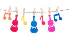 截去在麻线、垂悬的五颜六色的音符和吉他 库存图片