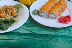 戳三文鱼用米和鲕梨在一个白色板材和寿司在绿色Kopi空间背景 库存图片