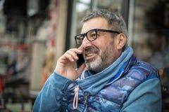 戴一个灰色胡子和眼镜的中年人谈话在MOBIL 图库摄影
