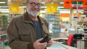 戴一个灰色胡子和眼镜的人在超级市场拿着一个整个钱包并且看照相机微笑 关闭 股票视频